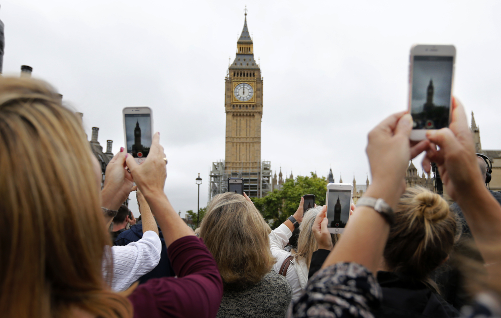 People record the last bell bong at Elizabeth Tower in London on Monday. At noon, Big Ben's famous bongs sounded for the last time before major renovation work is performed.