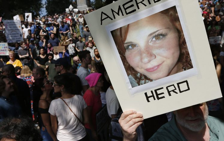 A counterprotester on Boston Common Saturday holds a photo of Heather Heyer, who was killed Aug. 12 in Charlottesville, Virginia, when an alleged Nazi sympathizer rammed a crowd of anti-racist protesters.