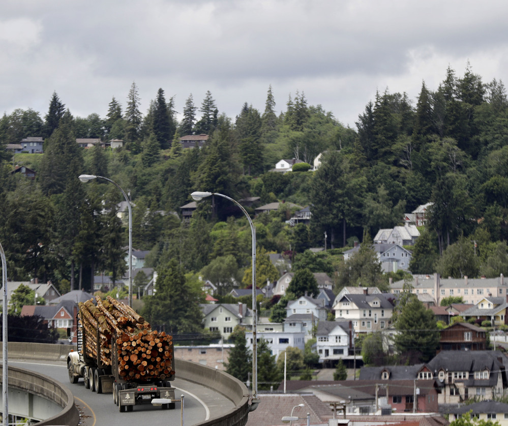 A logging truck makes its way through Aberdeen, Wash. The United States is importing more softwood lumber from overseas nations, including from Russia, data indicate.