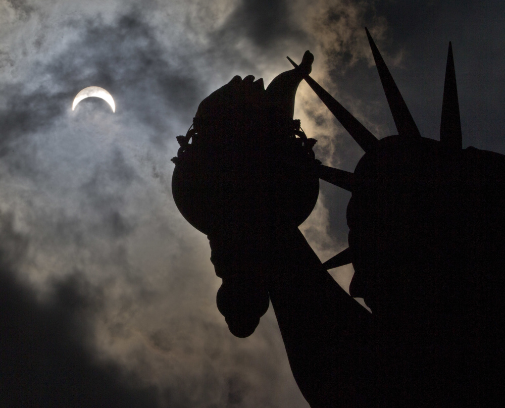 Day looks like night Monday afternoon in New York where the Statue of Liberty becomes a silhouette during the partial solar eclipse that briefly had much of the nation in the dark.