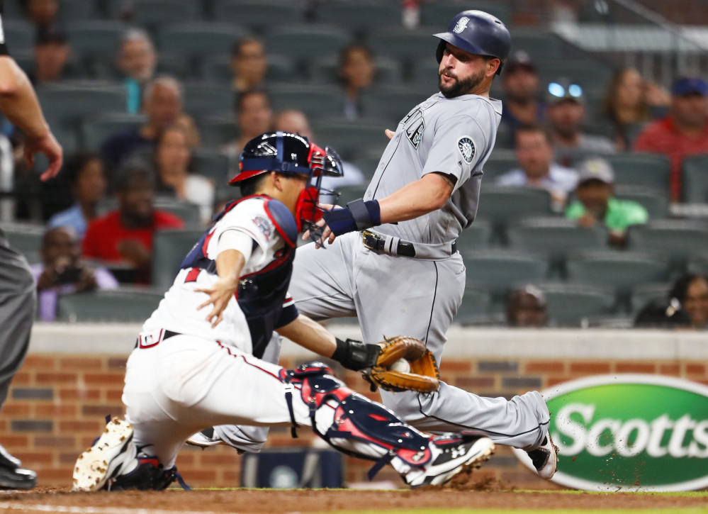 Yonder Alonso of the Mariners avoids the tag of Braves catcher Kurt Suzuki to score in the fourth inning Monday night in Atlanta. Seattle, which began the day 1 game out of a wild-card spot, won 6-5.