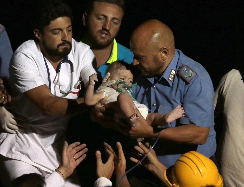 Rescuers pull out 7-month boy Pasquale from the rubble of a collapsed building in Casamicciola, on the island of Ischia, near Naples, Italy, on Tuesday.