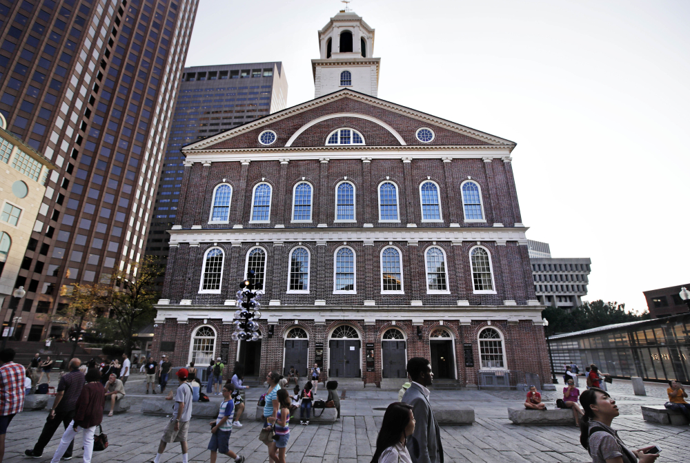 Pedestrians pass Faneuil Hall in Boston Monday. As U.S. cities grapple with what to do with Confederate monuments, some are suggesting renaming the historic hall,  given to the city by a wealthy merchant who traded slaves.