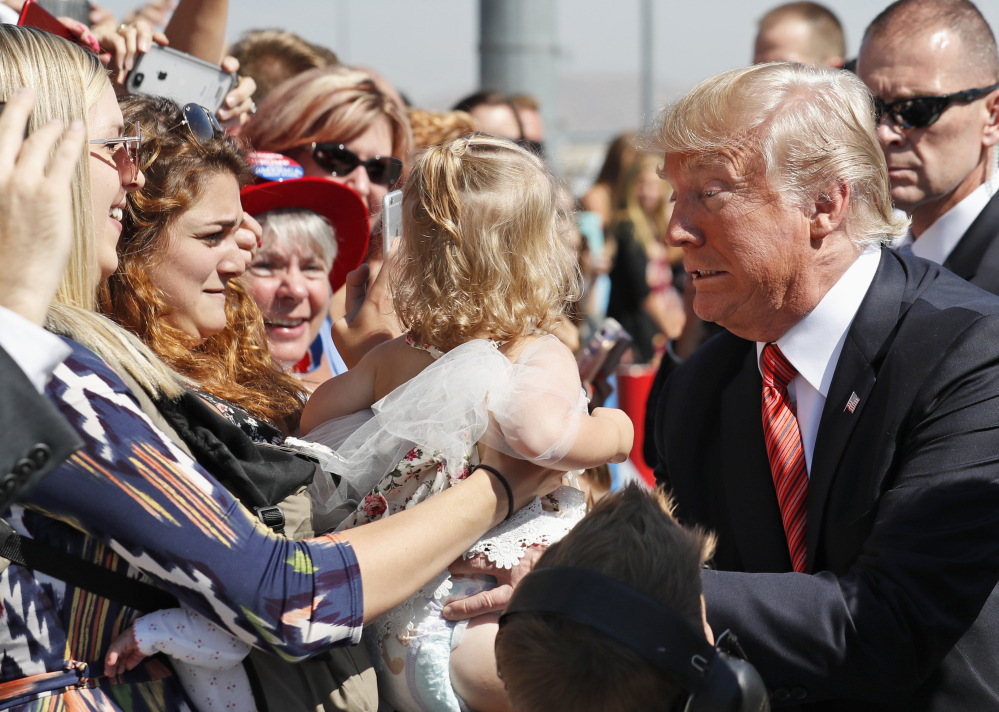 President Trump holds a baby as he greets supporters after arriving in Reno, Nev., on Wednesday.