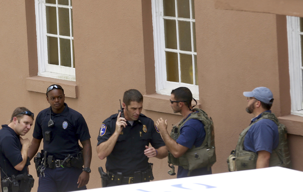 Police gather near the scene of a shooting in Charleston, S.C., on Thursday. Authorities say a disgruntled employee shot one person and was holding hostages in a restaurant in an area that is popular with tourists. The gunman was later shot by police.