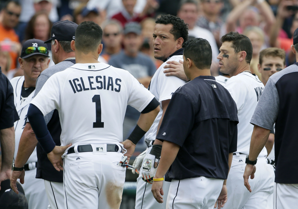 The Tigers' Miguel Cabrera looks back at the New York Yankees as he is guided off the field by teammate Ian Kinsler, right, and Jose Iglesias after a bench-clearing fight in the sixth inning of Thursday's game in Detroit.
