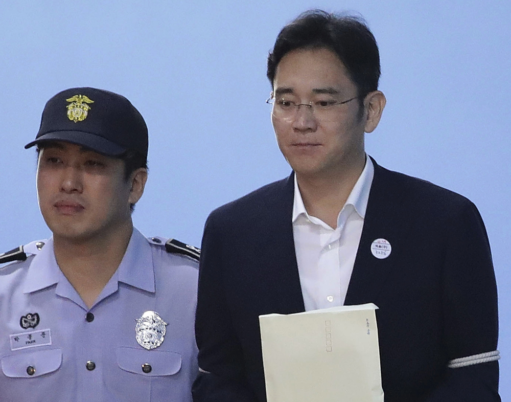 Samsung Electronics Co. Vice Chairman Lee Jae-yong, right, is escorted from Seoul Central District Court on Friday.