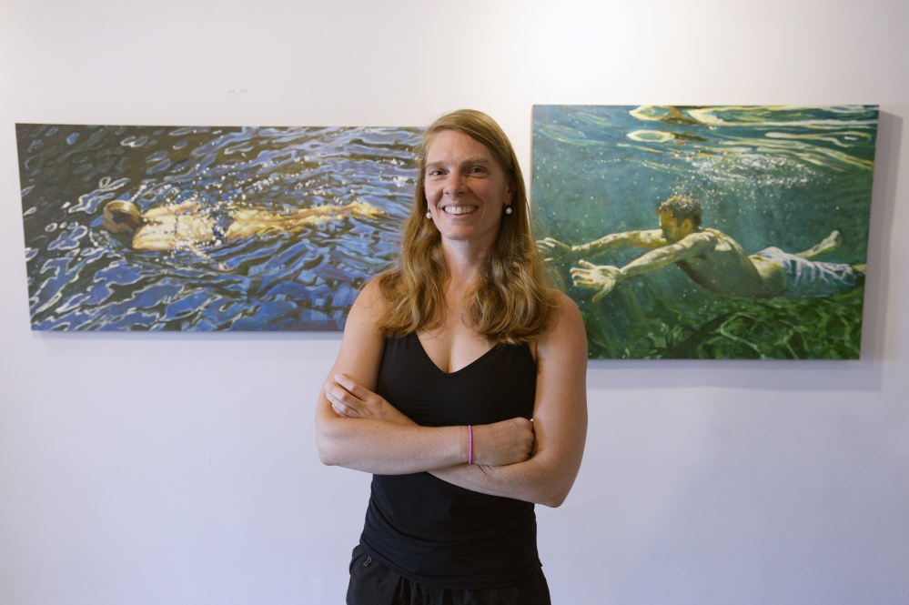 "Jessica Lee Ives in her Camden studio with two of her paintings, ""Watermark,"" left, and ""Become Alive."""