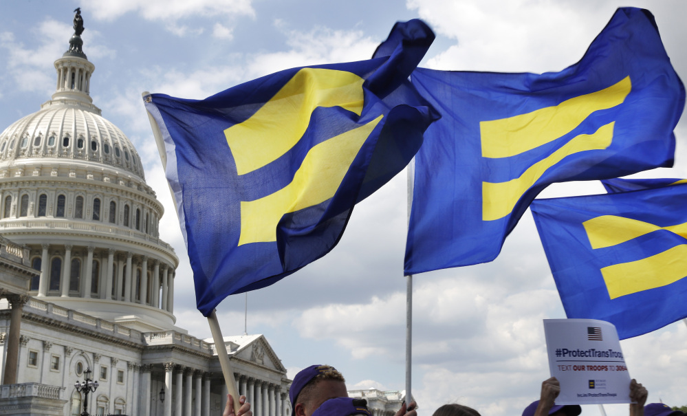 """People with the Human Rights Campaign hold up """"equality flags"""" during an event on Capitol Hill in Washington in July in support of transgender members of the military."""