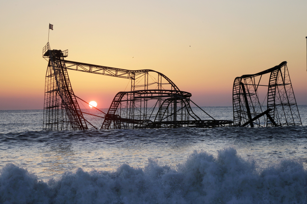 The sun rises behind the Jet Star Roller Coaster, sitting in the ocean on Feb. 25, 2013, after part of the Funtown Pier was destroyed during Superstorm Sandy in October 2012, in Seaside Heights, N.J.