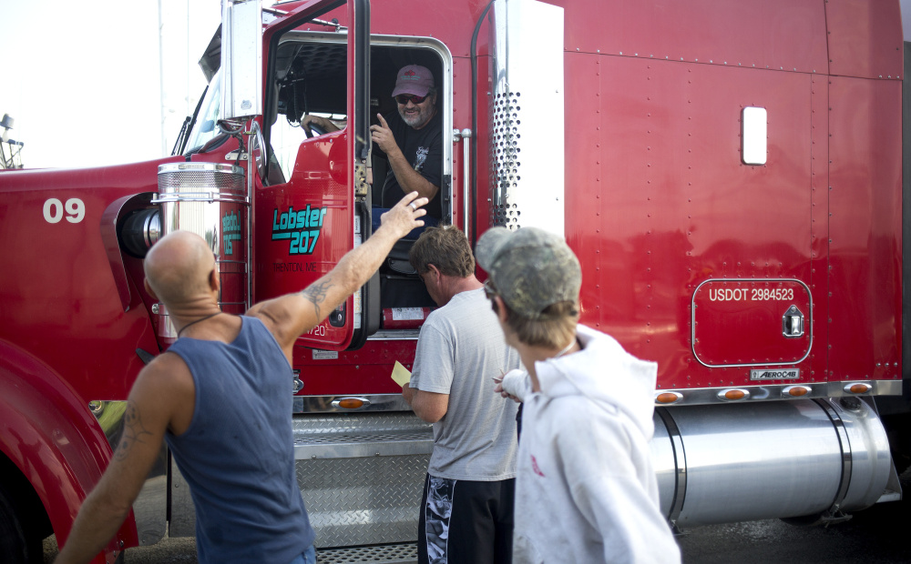 Dwayne Bradford, a union driver, waves to the Fox Island Lobstering crew after loading their union-caught lobster from Vinalhaven onto a union truck.