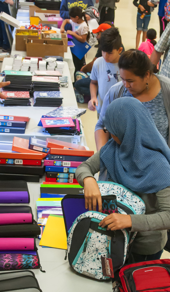 People choose backpacks and other school supplies Saturday at a giveaway at the Augusta Elks Lodge.