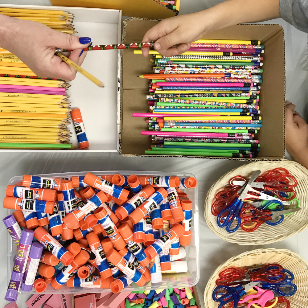 A volunteer, left, hands a pencil to a student during the backpack and school supplies giveaway on Saturday at Augusta Elks Lodge.