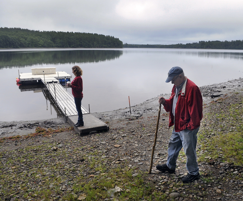 Stan Whittier walks on the shore of Clary Lake in Jefferson in 2015 while his daughter, Jane Roy, stands on the family's dock. It's been nearly five years since property owners in Jefferson and Whitefield appealed to the state to intervene over a low water level.