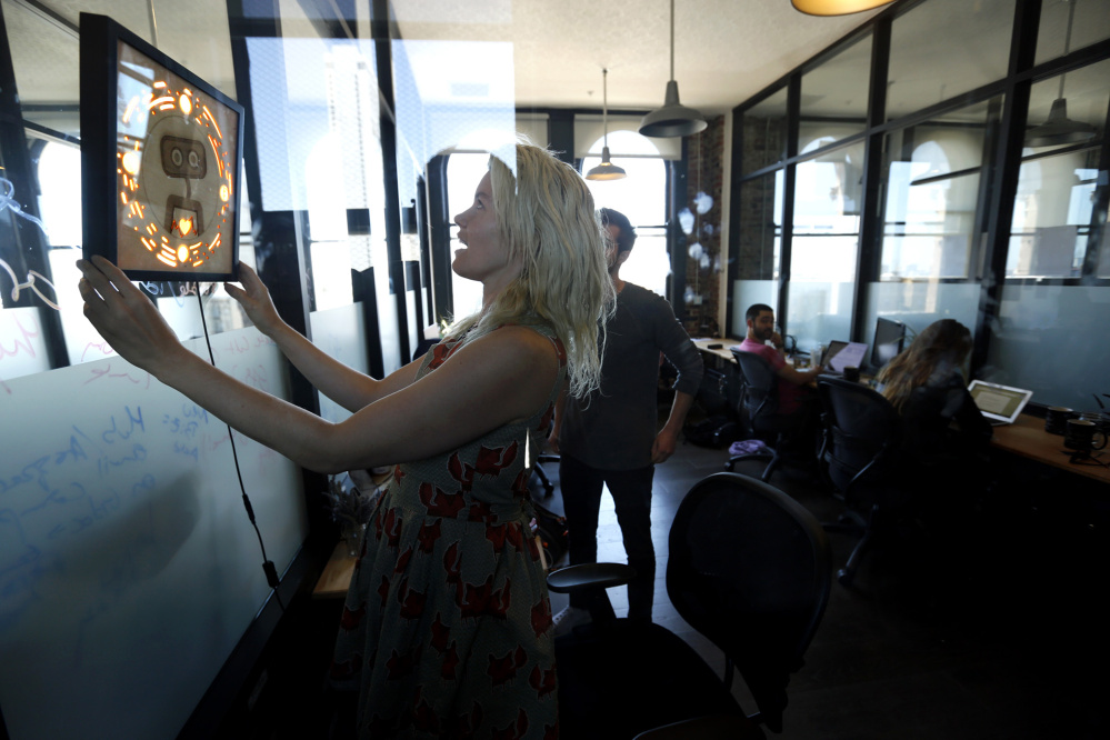 Pamela Fox, chief technology officer with Woebot, hangs a picture frame that contains the logo for the startup in San Francisco office. Woebot has created a chatbot that offers users cognitive behavioral therapy to help alleviate stress, anxiety and depression.