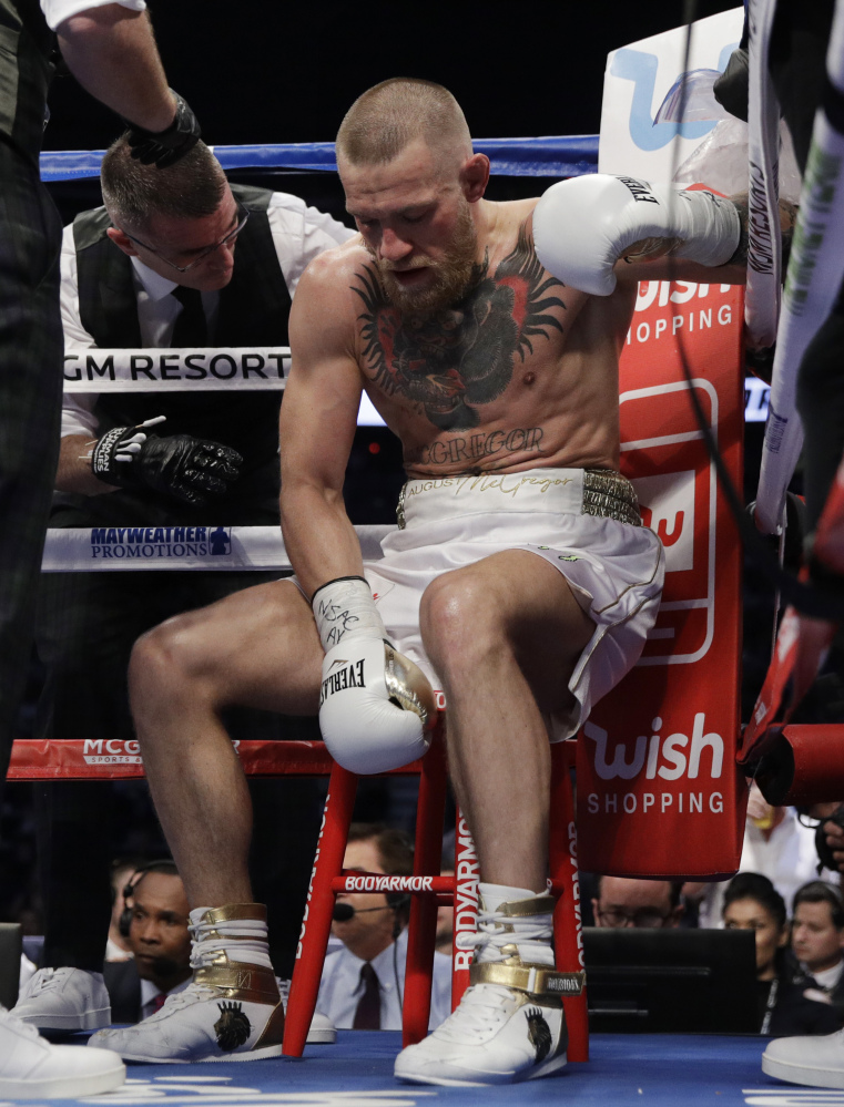 Conor McGregor sits in his corner between rounds of his super welterweight boxing match against Floyd Mayweather Jr.