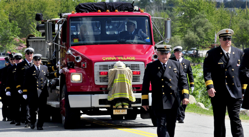 Former Fire Chief George Studley's helmet, boots and fire coat are mounted on a China Village firetruck Sunday for a procession of fire departments that made their way to the station for a last call ritual for Studley, who died Aug. 18.
