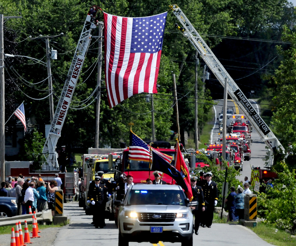 A memorial service procession of area fire departments makes its way Sunday under an American flag en route to the China Village fire station to honor the late former Fire Chief George Studley.