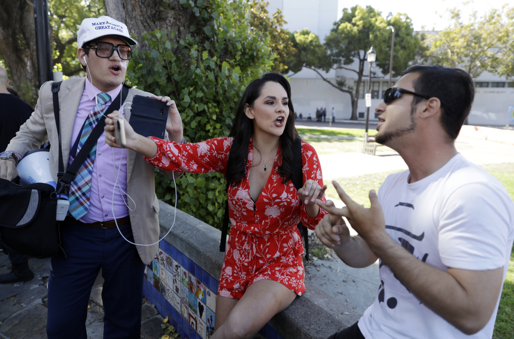 Donald Trump supporters Jovi Val, left, and Irma Hinojosa, center, argue opposing views with Alex Jones during a free speech rally Sunday in Berkeley, Calif. Several people were arrested during the demonstrations.
