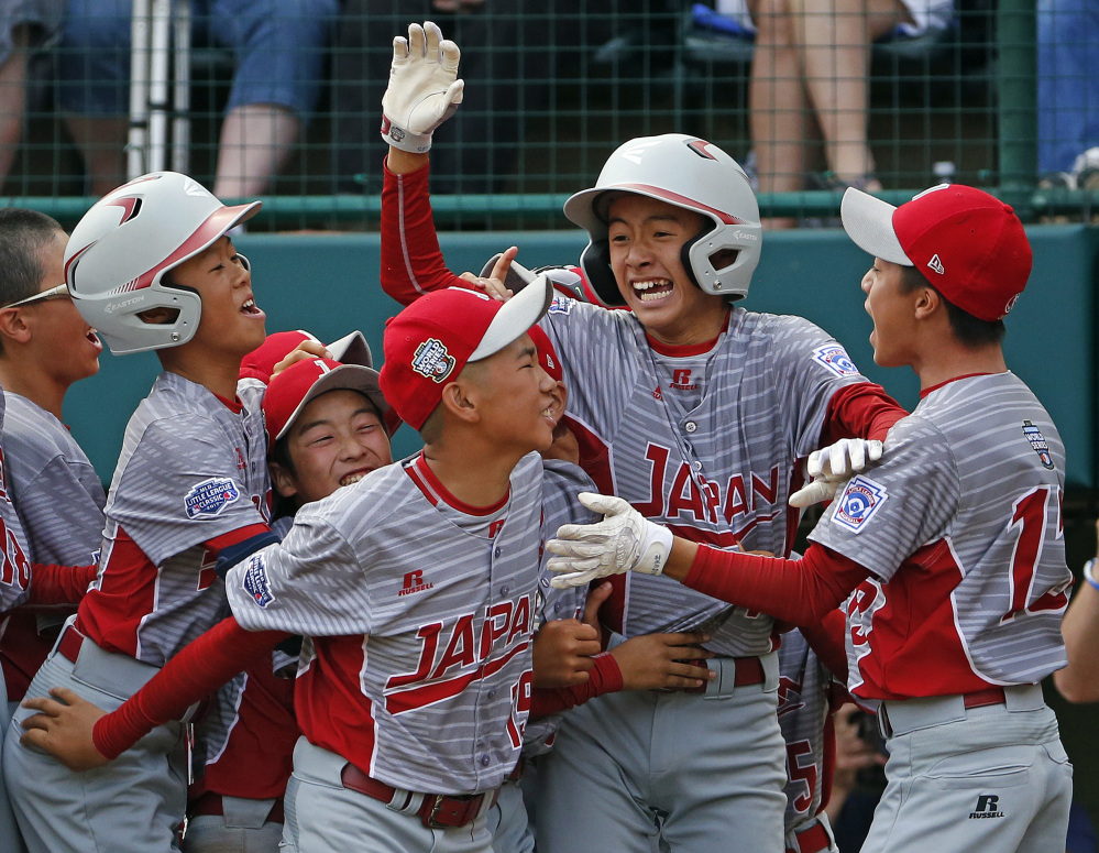 Japan's Seiya Arai, second from right, is surrounded by teammates after scoring the game-ending run against Texas in a 12-2 victory in the final of the Little League World Series.