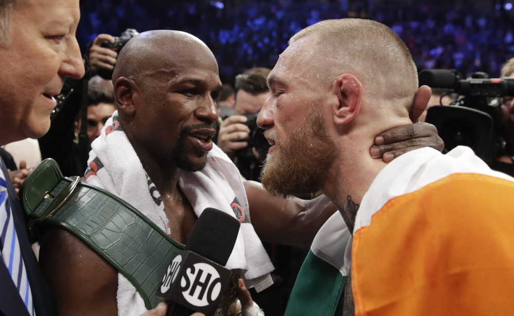 Floyd Mayweather Jr. embraces Conor McGregor after a fight that likely earned Mayweather more than $300 million and McGregor about $100 million.