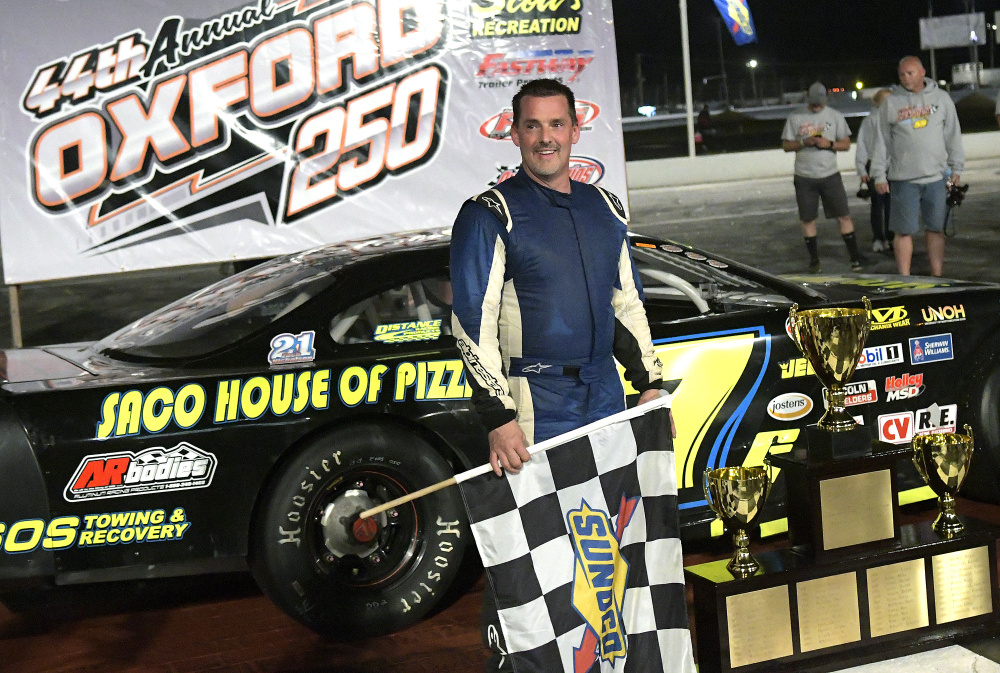Curtis Gerry of Waterboro holds the checkered flag after winning the Oxford 250 on Sunday at Oxford Plains Speedway. Staff photo by Andy Molloy
