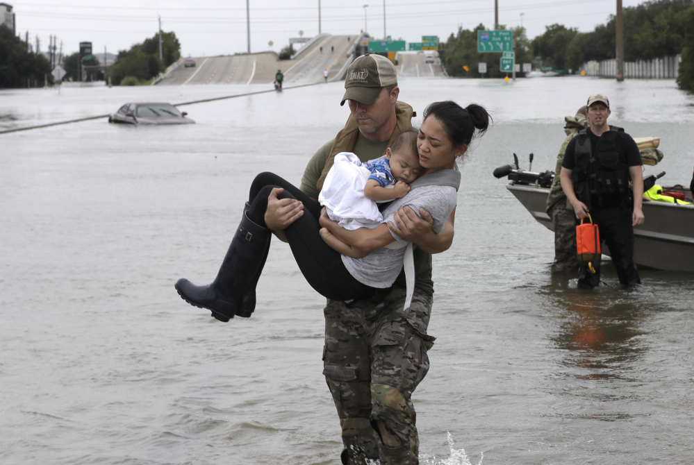 Houston Police SWAT officer Daryl Hudeck carries Catherine Pham and her 13-month-old son Aiden after rescuing them from their home surrounded by floodwaters from Tropical Storm Harvey Sunday in Houston. The remnants of Hurricane Harvey sent devastating floods pouring into Houston Sunday as rising water chased thousands of people to rooftops or higher ground.