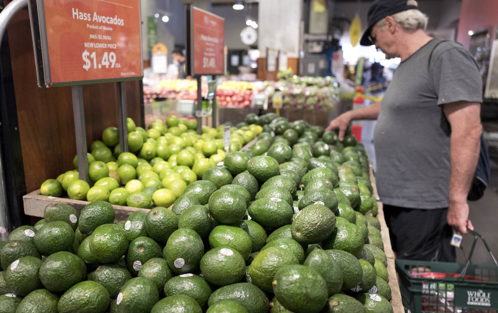 A customer shops for avocados at a Whole Foods on Monday in New York. Cutting prices at Whole Foods shows that Amazon is serious about taking on competitors such as Wal-Mart, Kroger and Costco.