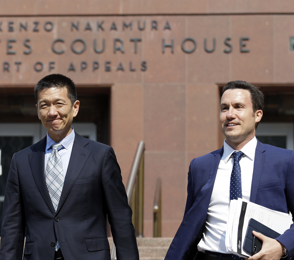 Hawaii Attorney General Doug Chin, left, smiles as he leaves a federal courthouse with assistant Joshua Wisch after appearing there Monday in Seattle.