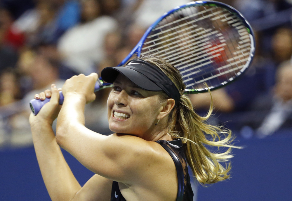 Maria Sharapova follows through on a shot Monday night during her three-set victory against second-seeded Simona Halep in the opening round of the U.S. Open.
