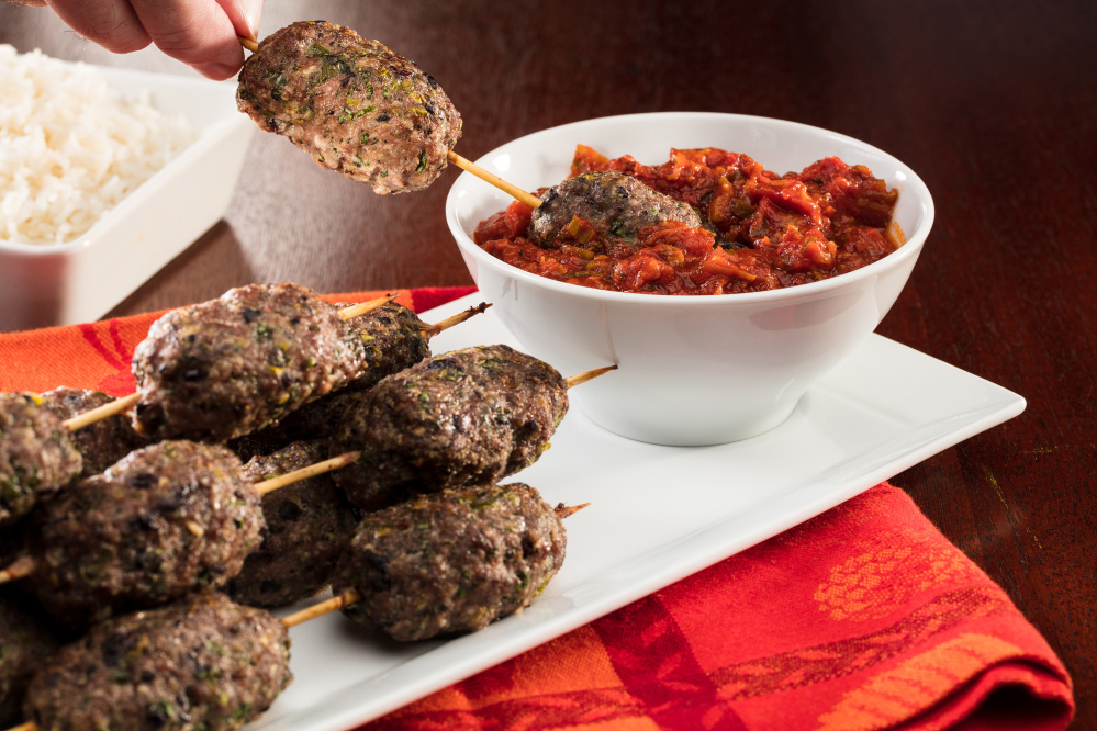 Lamb and Kalamata olive sausages are formed by hand, then skewered for cooking. Serve them with a minted tomato sauce.