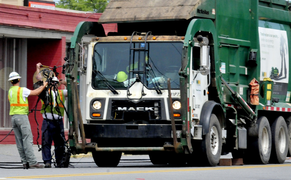 Workers pull a coil of wires off the hydraulic lifts of a Waste Management truck after the truck struck wires hanging low across College Avenue in Waterville on Tuesday. Police believe another truck snagged the wires and left the scene causing them to hang lower than usual and then the Waste Management truck hit the wires.