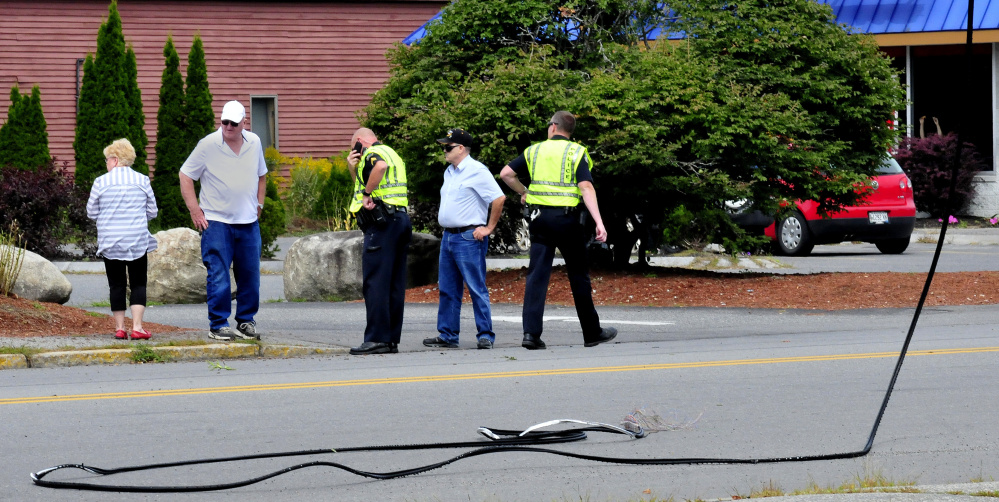 Waterville police interview witnesses near the site where they say two trucks hit and eventually snapped a communications wire across College Avenue in Waterville on Tuesday.