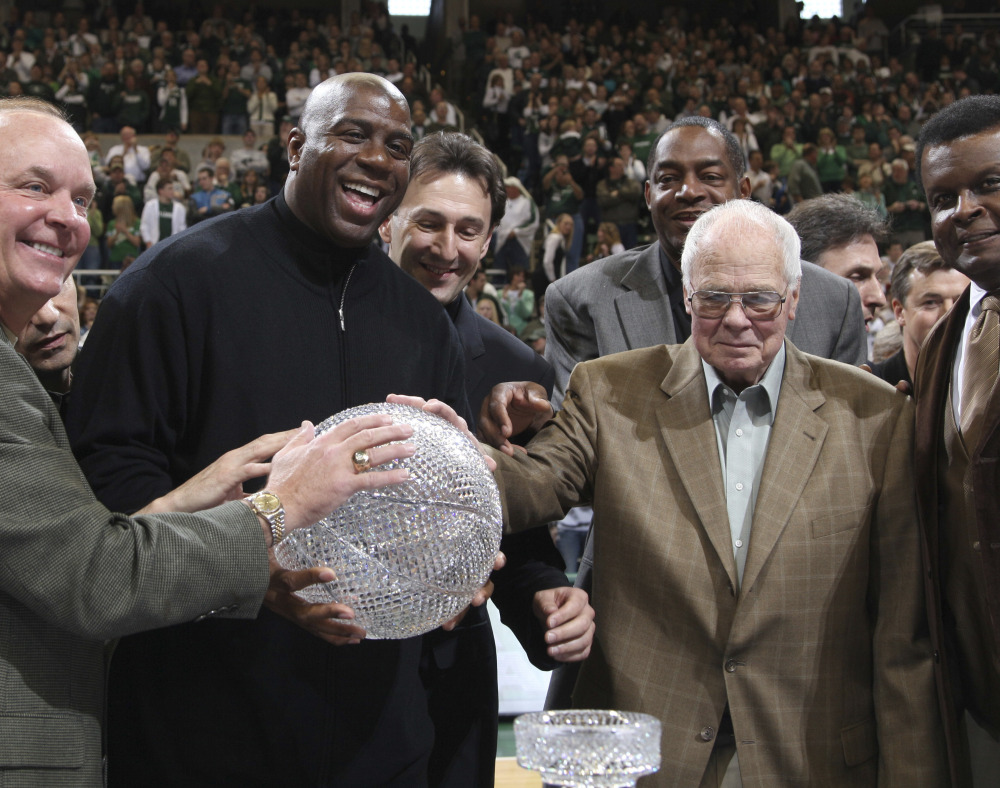 Thirty years after defeating the Larry Bird-led Indiana State team for the 1979 NCAA basketball championship, Magic Johnson, second left, and his teammates reunited with Coach Jud Heathcote at Michigan State. Heathcote died Monday at age 90.