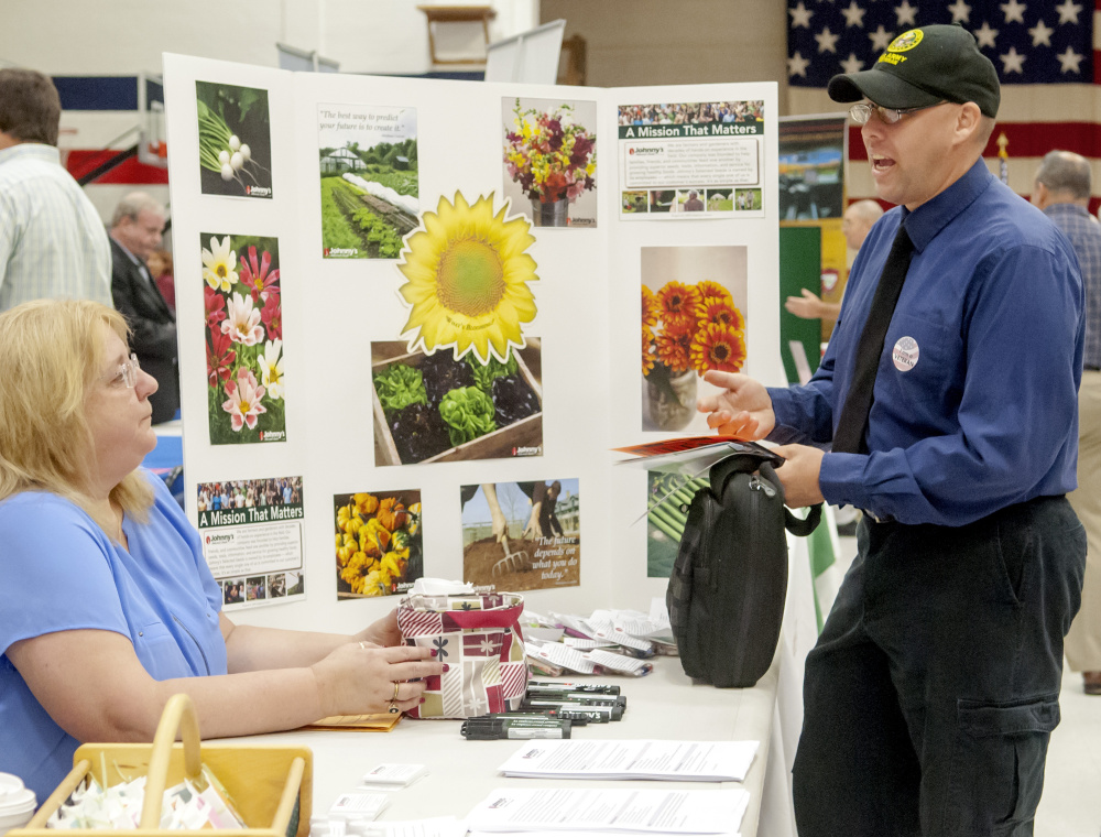 Cheryl Doucette, of Johnny's Selected Seeds, left, and Army veteran Franklin Smart, chat during job fair Tuesday at the Augusta Armory.