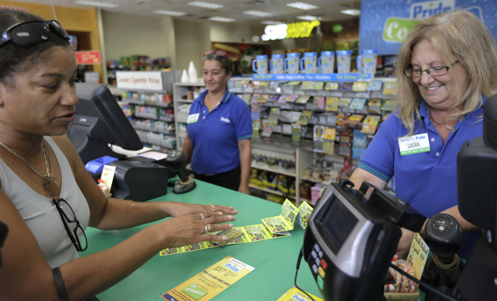 Valerie Williams, of Springfield, Mass., left, buys lottery tickets last week in Chicopee, Mass., where the winning ticket for a 'mega-millions' Powerball jackpot was sold.  was sold.
