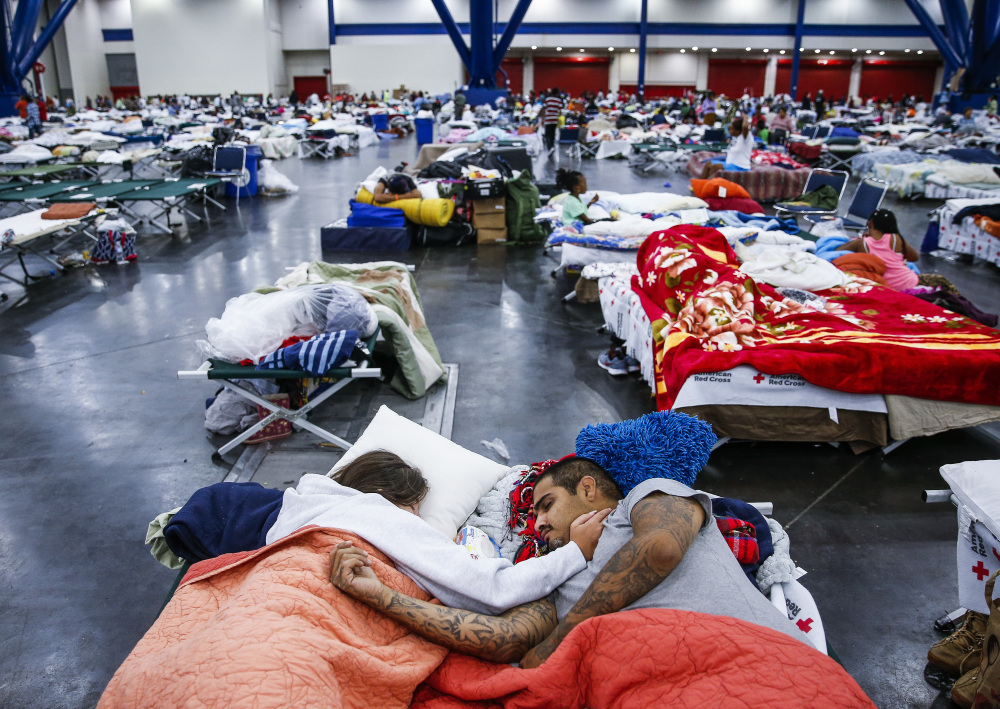 Tammy Dominguez and her husband, Christopher, sleep on cots at the George R. Brown Convention Center in Houston, where 10,000 people were taking shelter Wednesday.