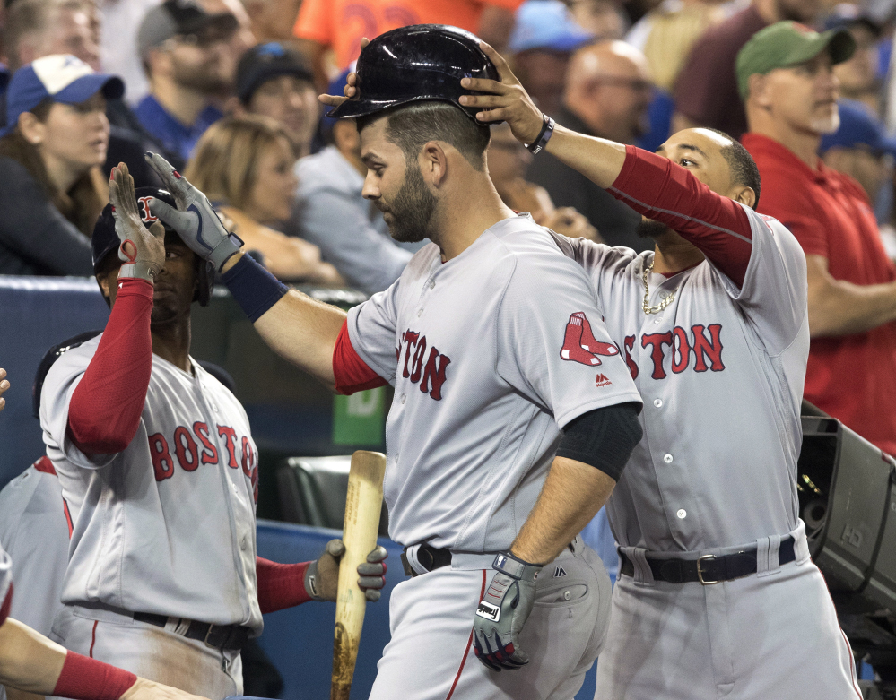 Boston's Mitch Moreland is congratulated after hitting a two-run home run against the Blue Jays in the seventh inning Wednesday night in Toronto.