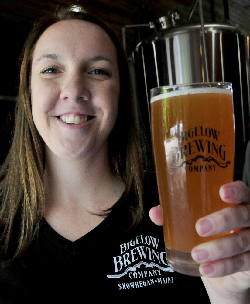 Bigelow Brewing Co. employee Jordan Powers shows off La Saison du Labrador beer, a collaboration of Bigelow and a Quebec brewery, that was brewed for Saturday's festival.