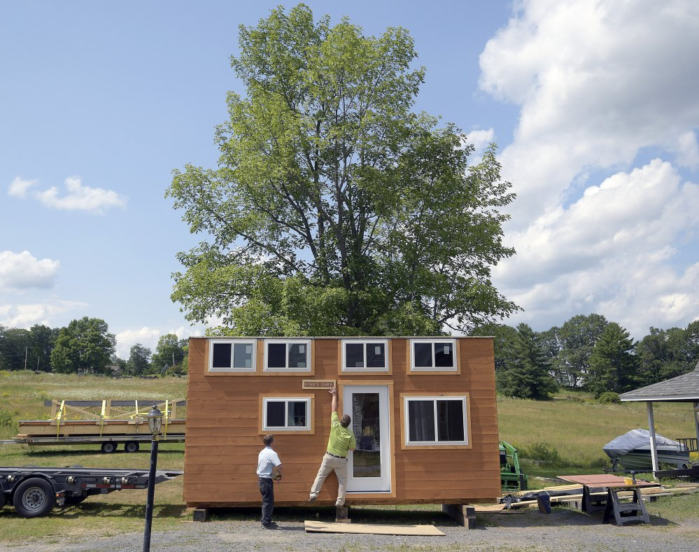 Pat Sirois removes a sign Monday from the tiny home built with sustainable Maine wood products at his home in Litchfield, as Brendell Martin prepares to load the home onto a trailer for a Make-A-Wish recipient.