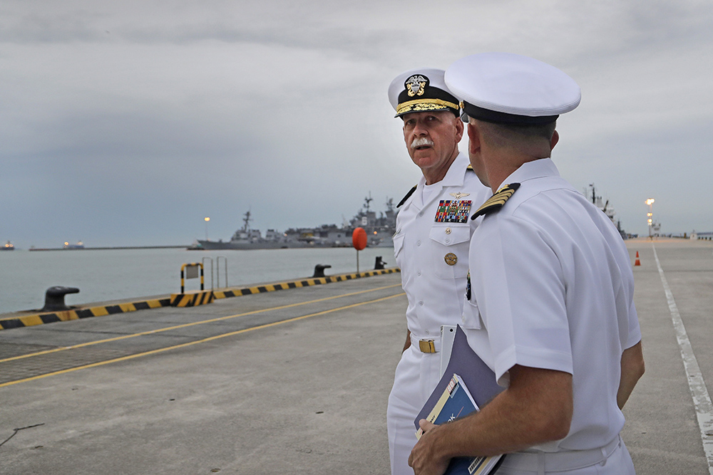 Commander of the U.S. Pacific Fleet, Scott Swift, left, arrives for a news conference at Singapore's Changi Naval Base on Tuesday. The USS John S. McCain and USS America are docked in the background.