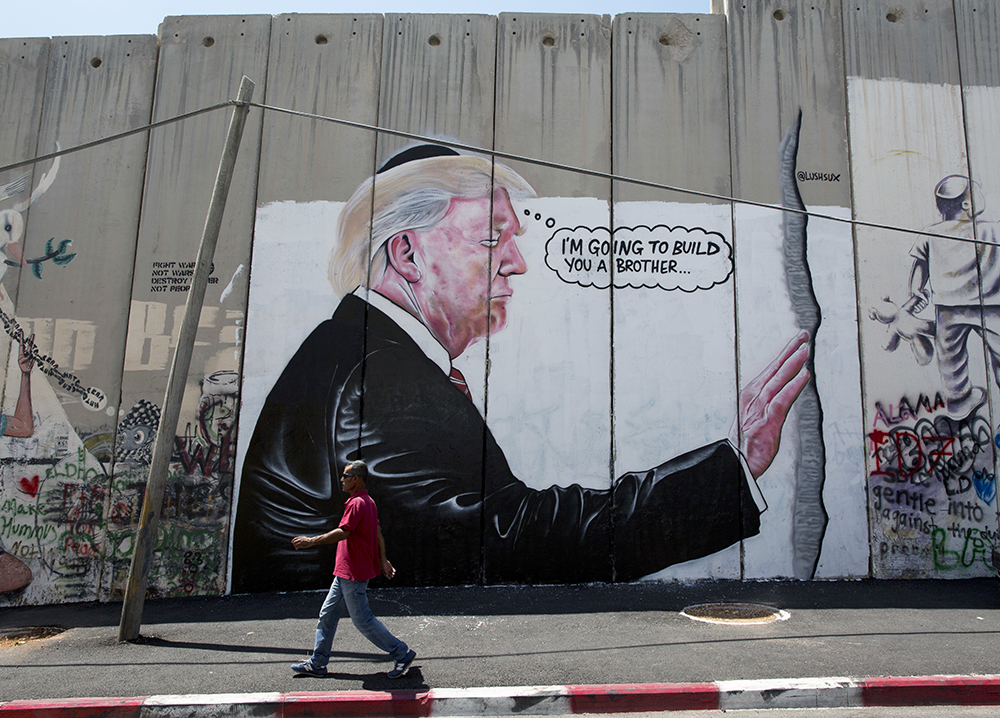 A mural resembling the work of the elusive artist Banksy depicts President Trump wearing a Jewish skullcap  on Israel's West Bank separation barrier in the city of Bethlehem.