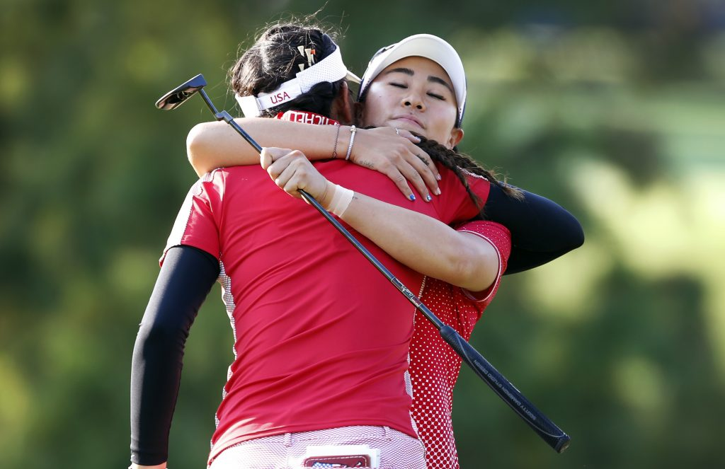 United States' Danielle Kang, right, gets a hug from teammate Michelle Wie after their four-ball match victory in the Solheim Cup golf tournament Friday in West Des Moines, Iowa.