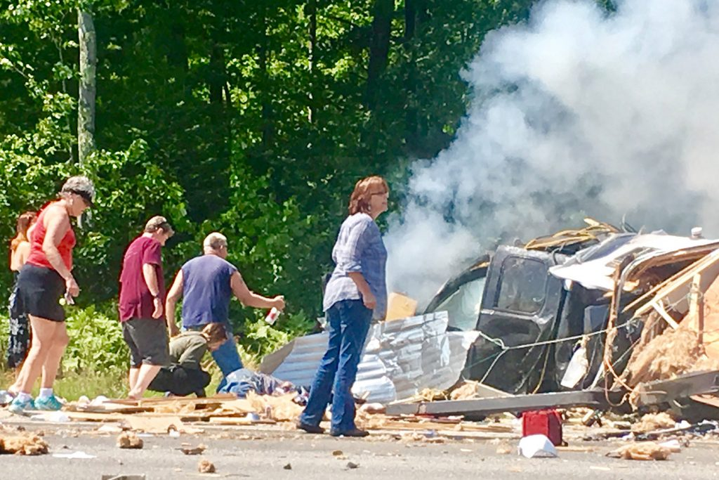 Passers-by converge to lend a hand moments after the crash on the Maine Turnpike near Exit 36 in Saco on Aug. 4.