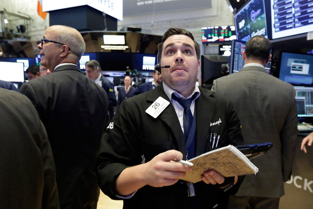 Trader Joseph Lawler works on the floor of the New York Stock Exchange on Tuesday. The Dow Jones industrial average continued to build on its record highs, and is closing in on 22,000.