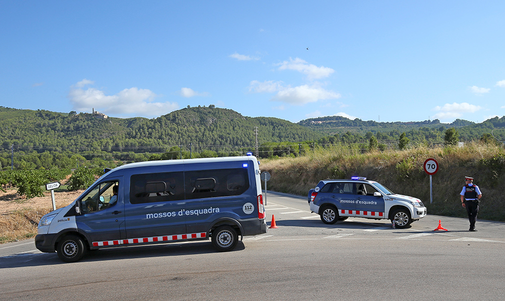 Catalan Mossos d'Escuadra officers and vans block a road near the place where a suspect was killed by police in Sant Sadurni d'Noia on Monday.