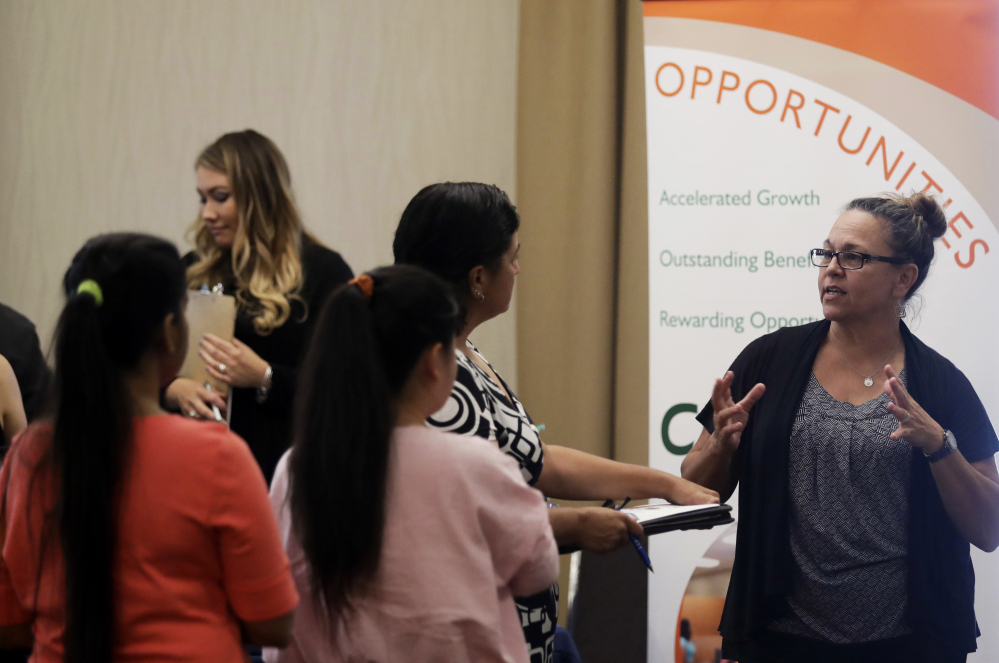 Kathy Tringali, right, a recruiter for retailer Big 5 Sporting Goods, talks to job seekers during a job fair in San Jose, Calif.