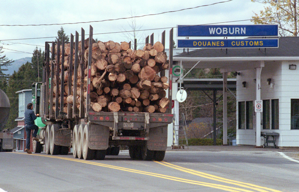 A logging truck enters Woburn, Quebec, from Coburn Gore, Maine. Canadian officials are looking to Gov. LePage to help convince President Trump not to raise new trade barriers that would disrupt commerce.