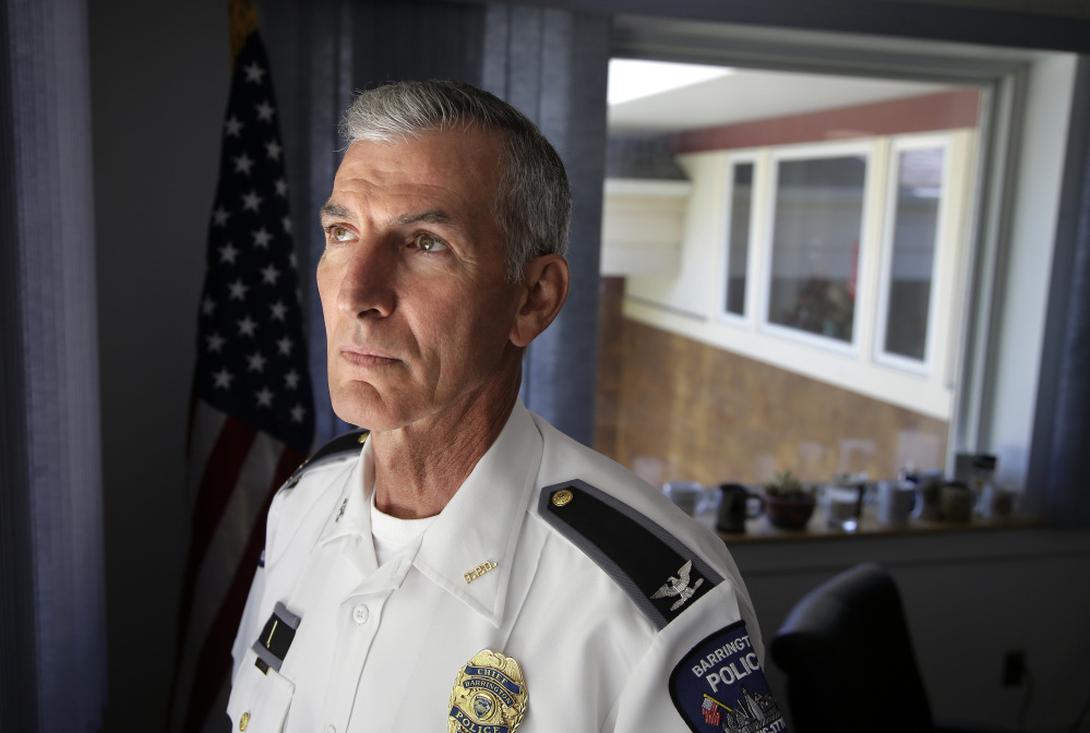 Barrington, R.I., Police Chief John LaCross stands for a photograph in his office. LaCross, who lost his brother to suicide in 1979, believes there is a growing trend of people turning to psychics after losing a loved one.