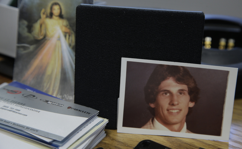 A photograph of Joseph LaCross rests near an image of Jesus on the desk of Barrington, R.I., Police Chief John LaCross at the police station in Barrington.